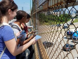 Three students stand on a bridge over a highway holding air quality monitors and taking notes