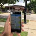hand holding a phone shows air monitor data