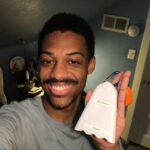 Person smiling holds an air quality monitor, which looks like a plastic cartoon ghost on a carabiner