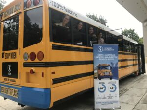 Smiling advocates enjoy a ride on an electric school bus